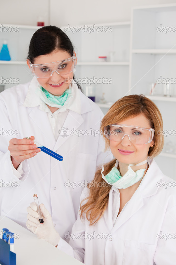 Female scientists with safety glasses looking at the camera in a lab  Stock Photo #10583967