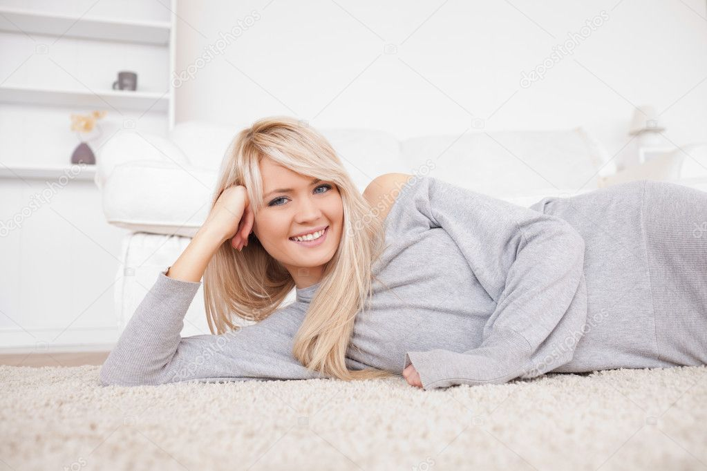 Attractive blond woman posing lying down on a carpet in the living room — Stock Photo #10586322