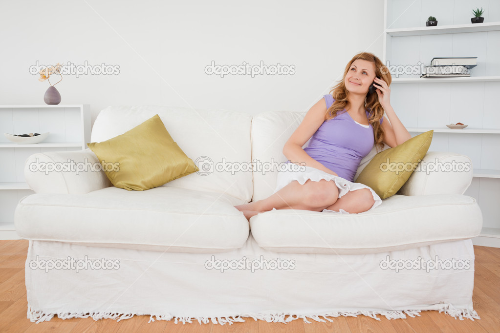 Beautiful red-haired woman on the phone sitting on a sofa in the living room — Stock Photo #10586843