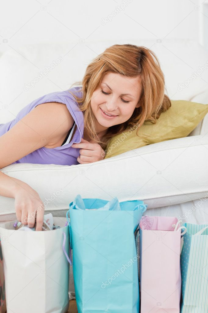 Attractive woman lying on the couch with her shopping bags in the living-room — Stock Photo #10587057