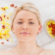 Attractive blonde woman lying down near flower petals — Stock Photo #10590818