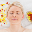 Delighted blonde woman lying down near flower petals — Stock Photo #10590827