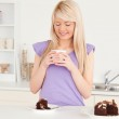 Attractive blonde woman eating cake and drinking coffee — Stock Photo