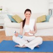 Smiling female having a rest after stretching while sitting on a — Stock Photo #10593513