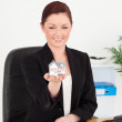 Young attractive red-haired woman in suit holding a miniature ho — Stock Photo #10595355