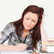 Beautiful red-haired girl being upset while studying for an exam — Stock Photo #10595669