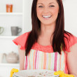 Beautiful red-haired woman holding some dirty plates in the kitc — Stock Photo