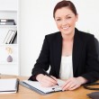 Beautiful red-haired female in suit writing on a notepad and pos — Stock Photo #10595801
