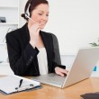 Young pretty red-haired female in suit typing on her laptop and — Stock Photo