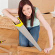 Good looking red-haired woman using a saw — Stock Photo