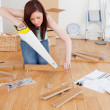 Good looking red-haired female using a saw for diy at home — Stock Photo