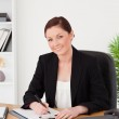 Beautiful red-haired woman in suit writing on a notepad and posi — Stock Photo #10597298