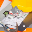 Tools and miniature house on an orange jacket — Stock Photo #10598448