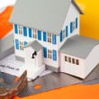 Tools and miniature house on an orange jacket — Stock Photo #10598486