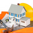 Tools and miniature house on an orange jacket — Stock Photo