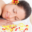Brunette and flowers petals in a spa - Stock Photo
