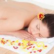 Young woman sleeping with flower petals around her — Stock Photo #10599101