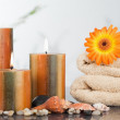 Lighted candles with an orange gerbera on towels and sea shells — Stock Photo