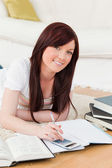 Attractive red-haired female studying for while lying on a carpe — Stock Photo