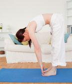 Attraktiva rödhårig kvinna stretching i vardagsrummet — Stockfoto