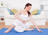 Good looking red-haired female stretching in the living room — Stock Photo