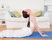Charming red-haired female stretching in the living room — Stock Photo