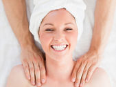 Closeup of a charming red-haired woman receiving a massage in a — Stockfoto
