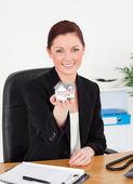 Jonge mooie roodharige vrouw in pak houden een miniatuur hou — Stockfoto
