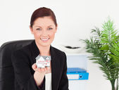 Young pretty red-haired woman in suit holding a miniature house — Stock Photo