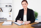 Attractive red-haired female in suit writing on a notepad and po — Stock Photo