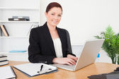 Young beautiful red-haired female in suit typing on her laptop — Stock Photo
