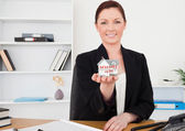 Young pretty red-haired female in suit holding a miniature house — Stock Photo