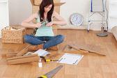 Hermosa chica pelirroja usando un martillo para bricolaje en casa — Foto de Stock