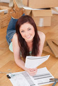 Good looking red-haired girl posing while reading a manual befor — Stock Photo