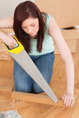 Attractive red-haired woman using a saw — Stock Photo