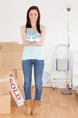 Krásný zrzavý žena držící miniaturní dům, stojící na — Stock fotografie