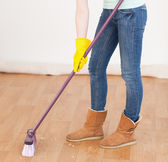 Attractive red-haired woman sweeping the floor at home — Stock Photo