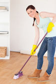 Good lookingl red-haired woman sweeping the floor at home — Stock Photo