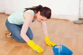 Gorgeous red-haired woman cleaning the floor while kneeling — Stock Photo