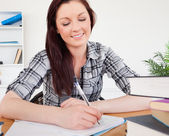 Lovely red-haired female studying at her desk — Stock Photo