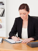 Beautiful red-haired woman in suit writing on a notepad — Stock Photo