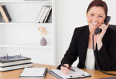 Pretty red-haired woman in suit writing on a notepad and phoning — Stock Photo