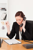 Infuriated beautiful red-haired woman in suit phoning — Stock Photo