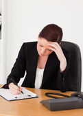 Depressed beautiful red-haired woman in suit writing on a notepa — Stock Photo