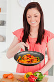 Attractive red-haired woman cooking vegetables in the kitchen — Stock Photo