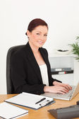 Young attractive red-haired woman in suit typing on her laptop a — Foto Stock