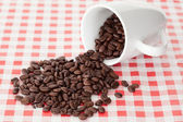 Spilled cup of coffee beans — Stock Photo