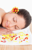 Brunette and flowers petals in a spa — Stock Photo