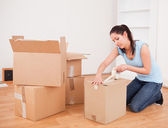 Pretty woman taping a box kneeling — Stock Photo