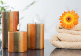 Lighted candles with an orange gerbera on towels — Stock Photo
